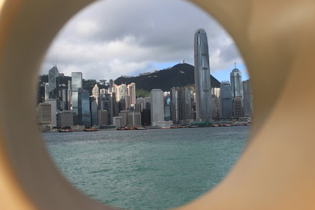 Art of Eye Peeping overlooking Victoria Harbour and the modern architecture of Skyscrapers along Hong Kong Island from Tsim Sha Tsui, Kowloon, Hong Kong