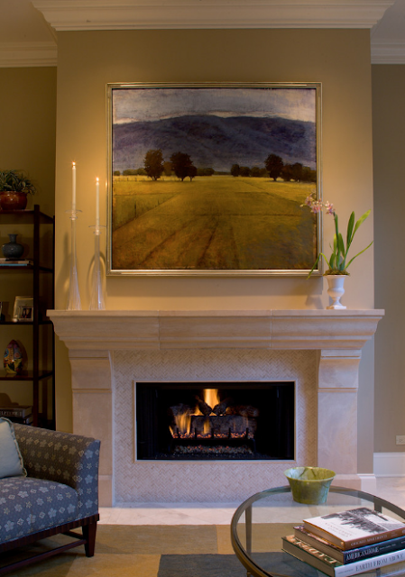 Photo of an updated fireplace with white marble surround and limestone mantle