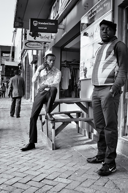A man looks on as another man makes a telephone call in Long street Cape Town