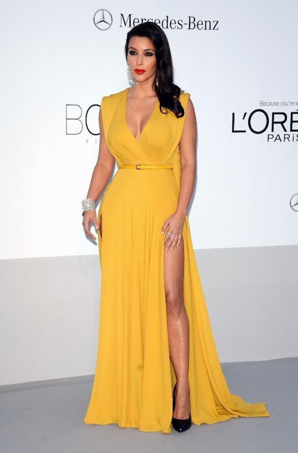 Kim Kardashian posing for photographers in a yellow dress