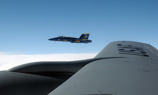 F/A-18 Hornet over the wing of  a KC-135 Stratotanker.
