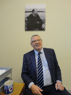 Brian Ervine sitting under a portrait of his late brother David Ervine