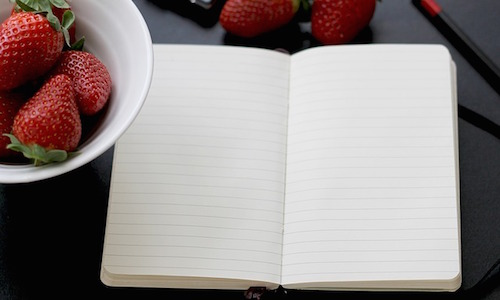 Workout log next to a bowl of strawberries