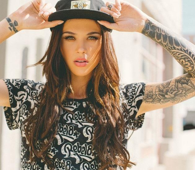 Modelo de mirada penetrante, posando se sujeta su gorra vemos tatuajes en sus brazos