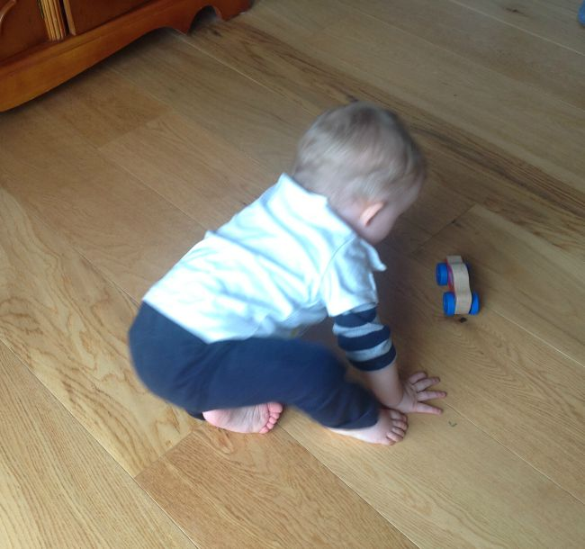 baby on floor playing with toy car