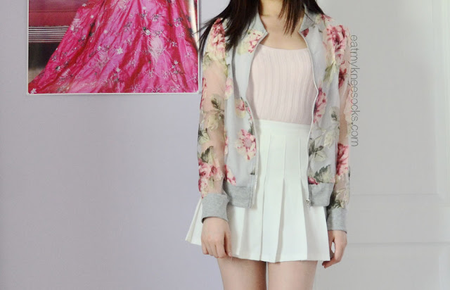 An ulzzang-inspired spring outfit featuring the Dresslink sheer floral jacket, a white pleated American Apparel tennis skirt, and a cropped pastel knit top.