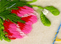 Close-up of the red rose. Red, pale pink and bright pink threads can be seen. Two different shades of green are used in the leaves and a white rosebud sits in the top right corner.