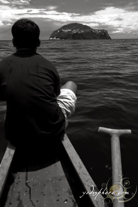 Solitary man on a boat approaching Bellarocca Resort at Elephant Island in Buenavista Marinduque Philippines