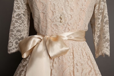 A guide to vintage lace wedding dresses, detail of bodice of classic 1950s lace wedding dress with satin ribbon belt