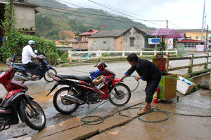 Washing motorbike outside a shop