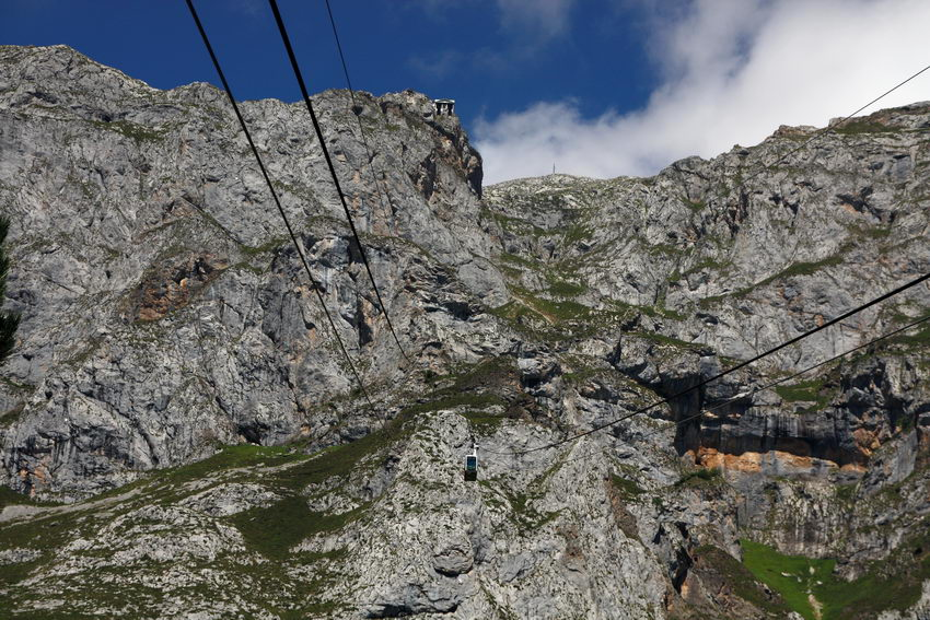 Fotografia tirada de dentro da cabine do teleférico, mostrando a montanha, os cabos, outra cabine em sentido contrário e a estação no cimo do monte