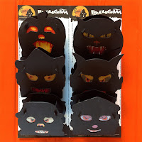 Open package shows Jack O'Lantern, witch, scarecrow, black cat, devil, and clown characters ready for eerie candlelight moods.