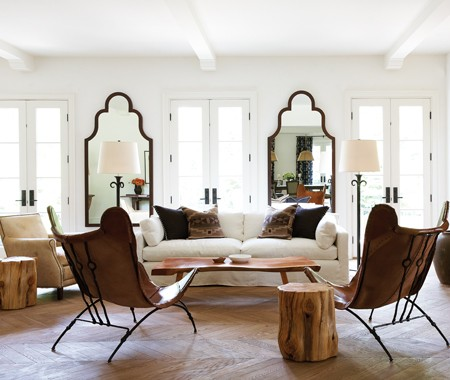 Living room with French doors, visible beams, Moorish floor mirrors, two leather butterfly chairs, reclaimed wood stools, light colored herringbone wood floors and a white upholstered sofa