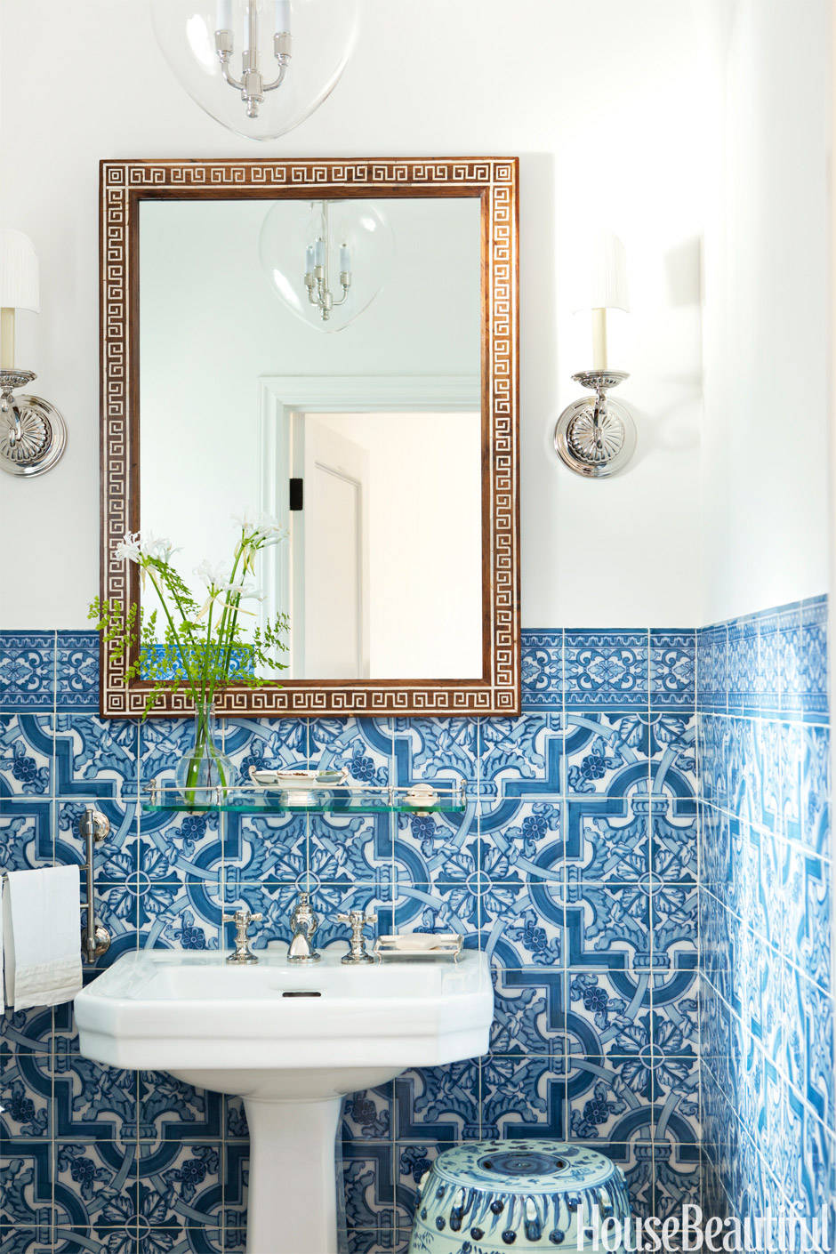 hand painted portuguese tiles bring drama to the powder room indian bone mirror from john rosselli