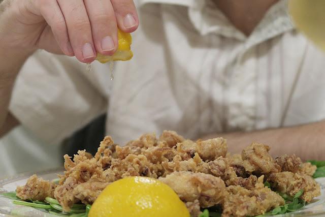 Squeezing lemon juice on calamari