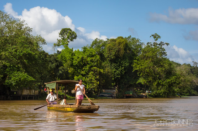 Local people in a wooden boat on Rio San Juan.