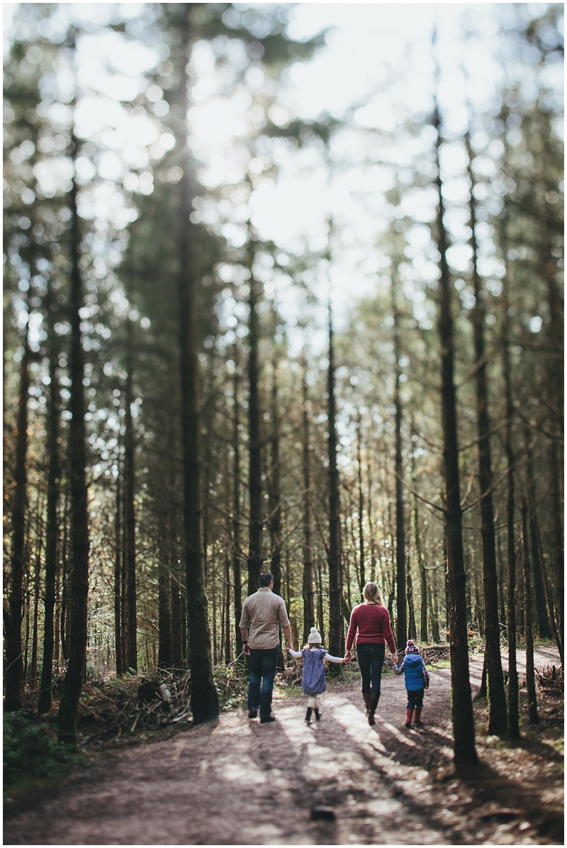 A family walking through tall trees together holding hands