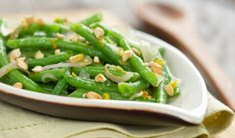 Mooi groene boontjes beetgaar gekookt en gemengd met aangestoofde sjalot, honing, citroensap en cashewnoten