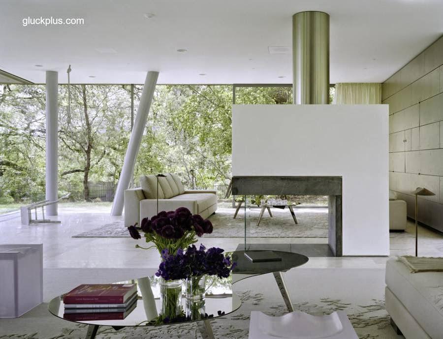 Sala de estar en amplio open plan a nivel del terreno debajo del volumen flotante de la planta superior de la moderna residencia