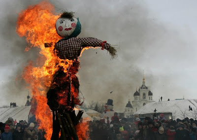 scarecrow burning in frontt of a large crowd