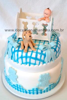 Bolo decorado chá de bebê, com o bebê no bercinho, o cachorro e decoração em  xadrez azul e branco com lacinhos e patchwork de ursinhos com barrado xadrez.