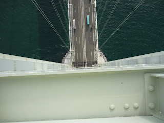 View looking stright down about 249 meters of tower on the Akashi Kaikyo bridge. The side of the tower looks perfectly straight and a few trucks visible on the roadway. Cables supporting the roadway and the ocean are also visible