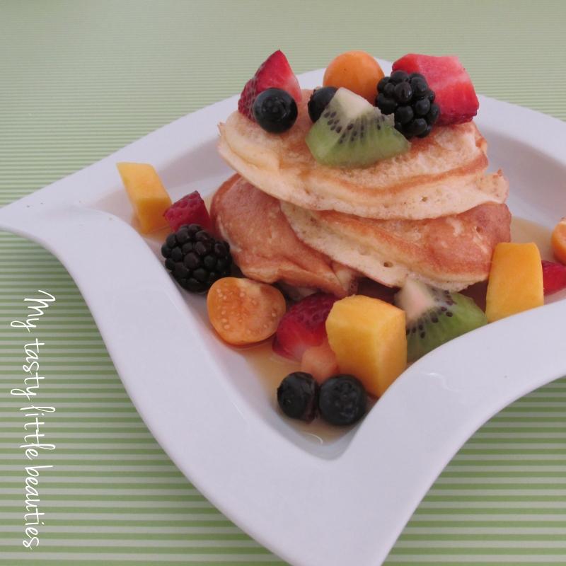 Pancake Stapel auf einem weißen Teller mit viel buntem Obst