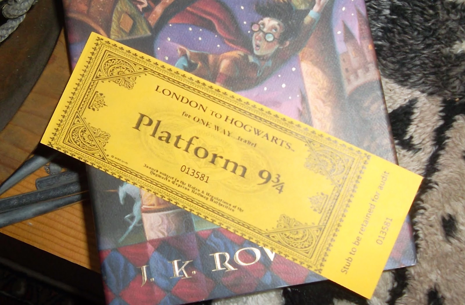 Hogwarts Express travel-ticket bookmark on top of Harry Potter and the Sorceror's Stone by J.K. Rowling