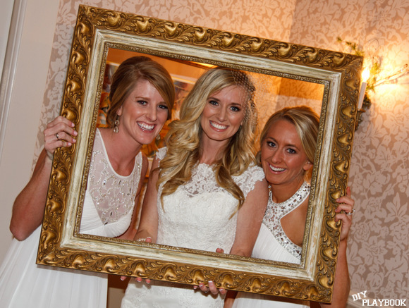 This happy bride poses with her bridesmaids and a large gold frame.