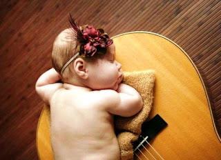 Bayi lucu menggemaskan tidur di atas gitar