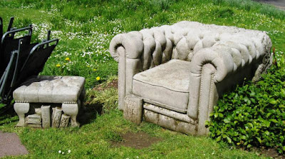 A sofa and footstool sculpted from stone