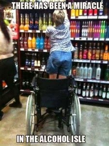 Woman in wheelchair viewed from behind, standing up to get a bottle of alcohol off a store shelf. Caption says there has been a miracle in the alcohol isle.