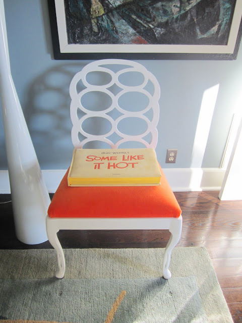 "Glossy white Elkins chair with bright orange upholstered seat with a copy of ""Some Like It Hot"""