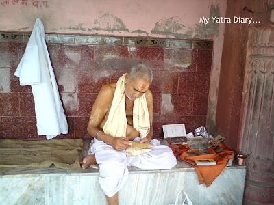 A priest reading a holy text at the Yamuna River Ghat, Mathura