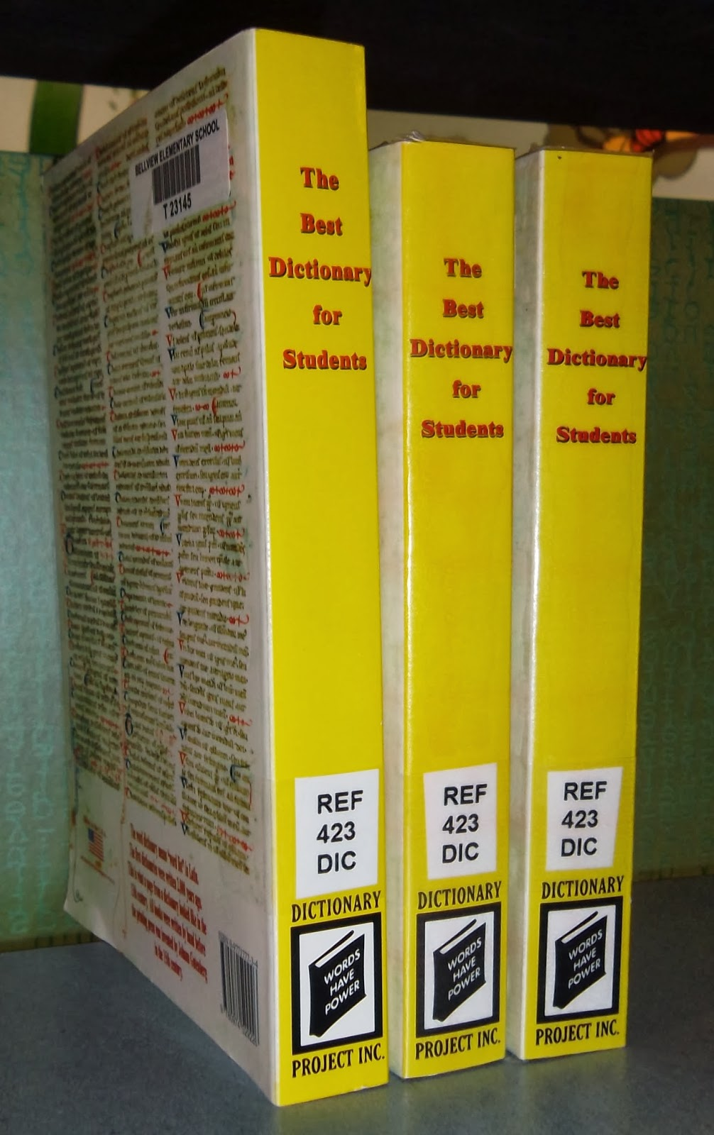 "A view along the spines of three dictionaries, The Best Dictionary for Students, each bearing a spine label stating ""REF 423 DIC."" A library barcode is visible on the back cover of the left-hand book. The books' spines also bear the name and logo of Dictionary Project, Inc."
