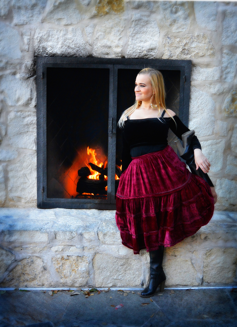 petite blonde posing with velvet skirt in front of fireplace