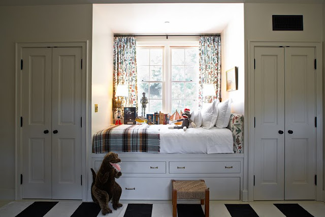 Built in window bed with white under bed drawers doubles as a window seat and reading area in a white bedroom with a black and white stripped rug,