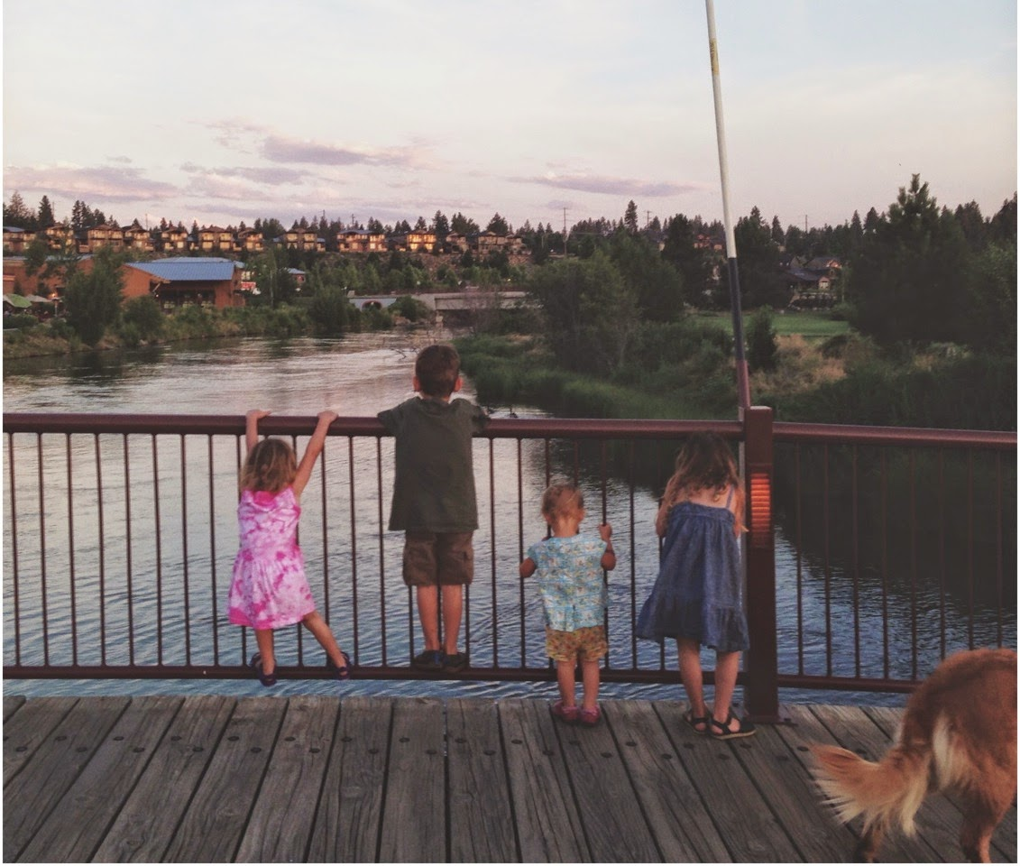 kids looking over a bridge into water