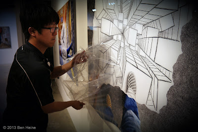 Ben Heine Art Exhibition : Removing the protective film from the signed acrylic Lamina Pencil Vs Camera prints