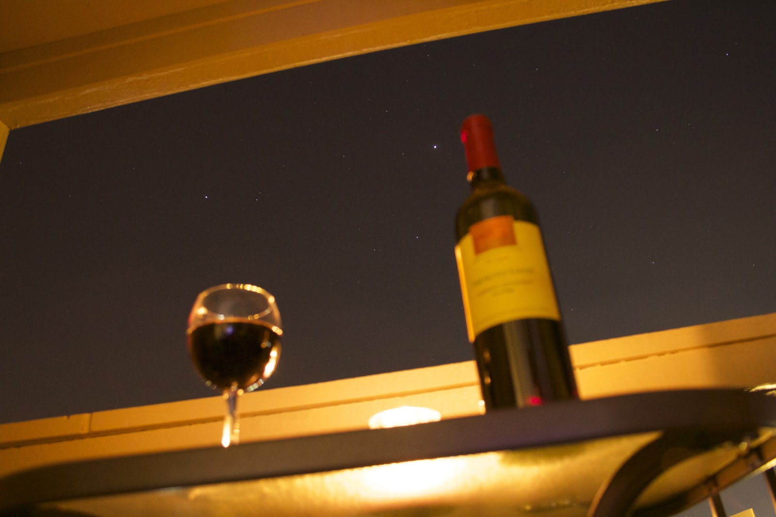 wine bottle and wine glass in front of stars background