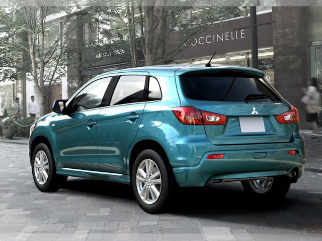 Rear 3/4 view of 2011 Mitsubishi Outlander sport driving on city street