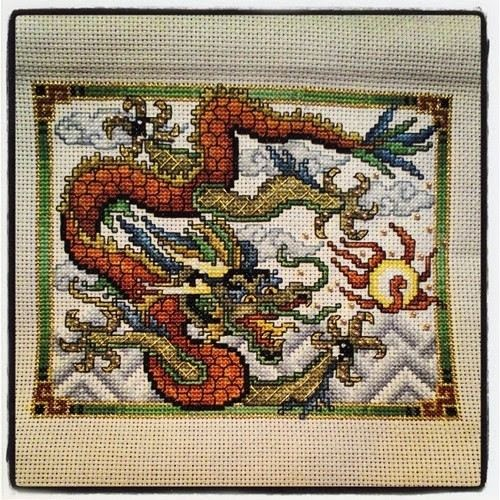 A cross stitch mountain dragon in shades of orange and green