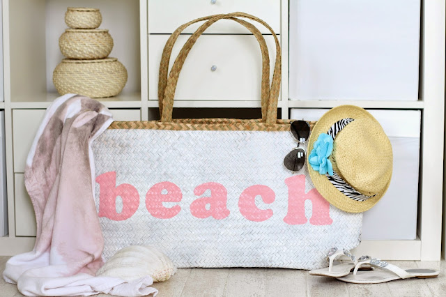 Großansicht Strandtasche mit Schriftzug Beach dekoriert mit Strandhut Sonnenbrille Flip Flops und einem Strandlaken
