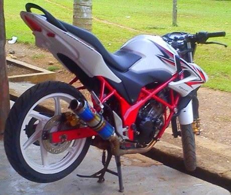 otoasia.net - Modifikasi minimalis Honda CB150R dengan perpaduan warna putih dan merah dibeberapa bagian menjadikan tampilannya semakin mentereng. Sang pemilik,  Ompong Ae Lach memang mengubah tampilan motornya mengusung konsep treetFighter supaya, tampil lebih gahar.