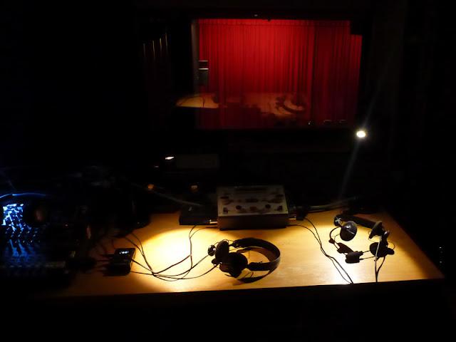 Ein Dolmetschpult, zwei Kopfhörer, links daneben ein Tonmischpult, vor einer Scheibe, die auf einen Kinosaal hinausgeht. Roter Vorhang ...