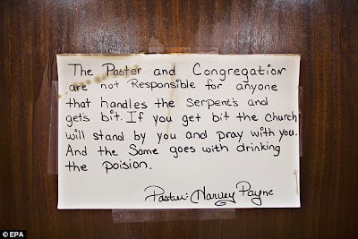 A handwritten sign on the altar warns members of the consequences of picking up snakes and drinking strychnine.