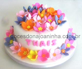 Bolo infantil decorado com flores coloridas: rosa lilás, amarelo, laranja e o nome da aniversariante.