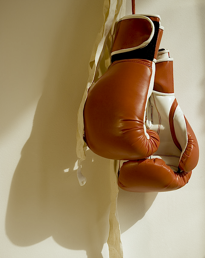 Red boxing gloves casting a shadow as they hang on a wall