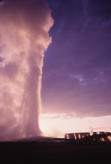 Geyser eruption of Old Faithful at Yellowstone National Park at dusk