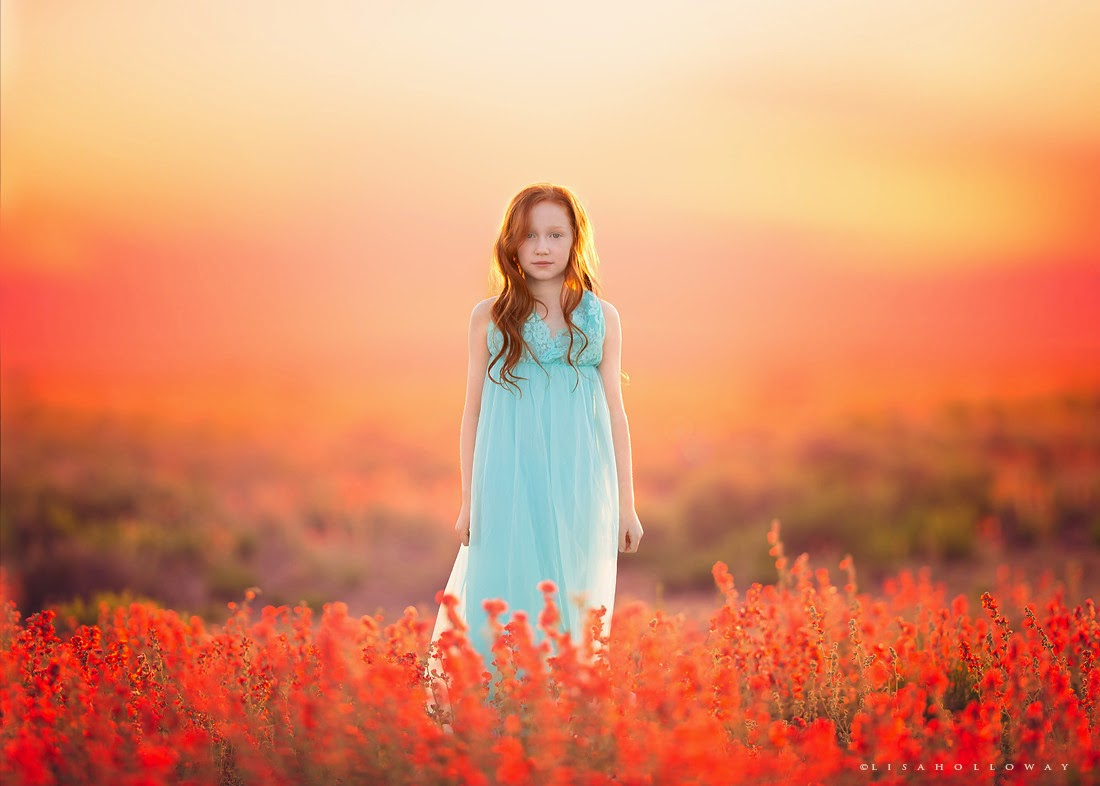 photo de Lisa Holloway représentant une jeune fille rousse en robe bleu pale au milieu de fleurs rouges